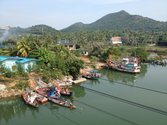 Thai fishing boats from a bridge over the river.